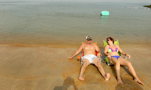 Michael Morganti and Lynn Roberts escape the heat Saturday on the mostly empty beaches of Fort Monroe.