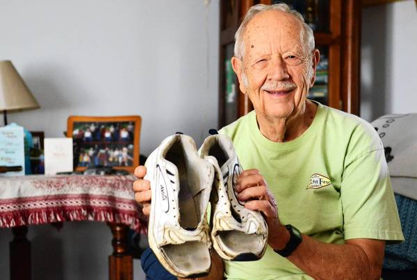 Donald Heffner shows his old sneakers after he's cut the front tops off to make a pair of sandals.