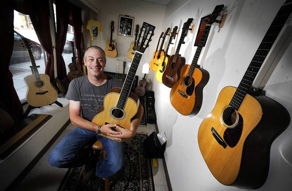 Shop owner Ed Golden holds a walnut 12-fret guitar that he made. He sits among high-end Martin guitars and other brands that he sells in his year-old Golden Guitar Gallery Thursday.