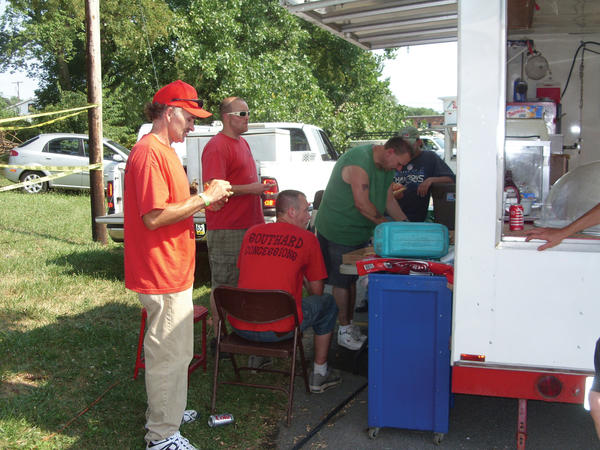Charles Southard, left, and other concession workers seek the shade of an awning during a break from activities Saturday afternoon at a fundraiser for St. Jude Children's Research Hospital at Williamsport American Legion Post 202.