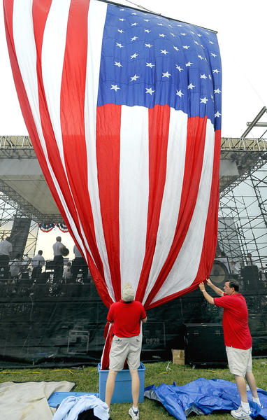 Workers raise the American flag behind the stage at the start of the MSO concert Saturday night at Antietam National Battlefield.
