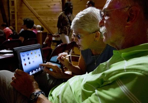 Demere and John Bates follow instruction on the iPad by Verizon representatives during a class at LifeLong Learning Society in Newport News. Verizon teamed up with the center to offer 3 free 1-hour wireless workshops for seniors.