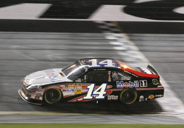 Tony Stewart crosses the finish line to win the Coke Zero 400 NASCAR Sprint Cup race at Daytona International Speedway on Saturday, July 7, 2012.