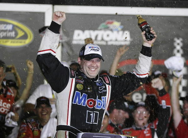 Tony Stewart celebrates in Victory Lane after winning the Coke Zero 400 NASCAR Sprint Cup race at Daytona International Speedway on Saturday, July 7, 2012.