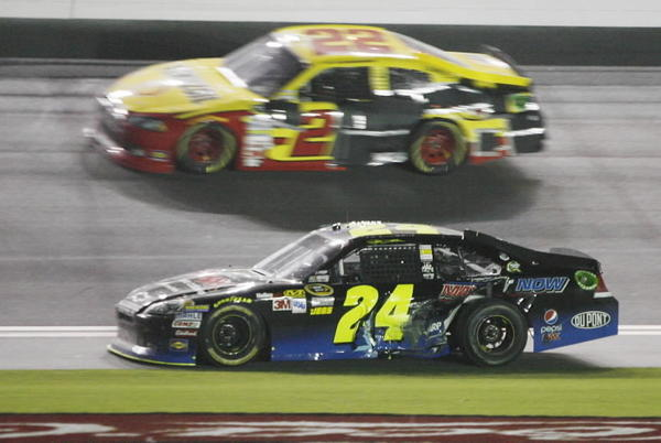 Sam Hornish, Jr. (top) and Jeff Gordon (bottom) cross the finish line during the Coke Zero 400 NASCAR Sprint Cup race at Daytona International Speedway on Saturday, July 7, 2012.