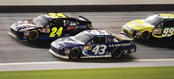 Jeff Gordon (24) races with Aric Almirola (43) and Carl Edwards (99) during the Coke Zero 400 NASCAR Sprint Cup race at Daytona International Speedway on Saturday, July 7, 2012.