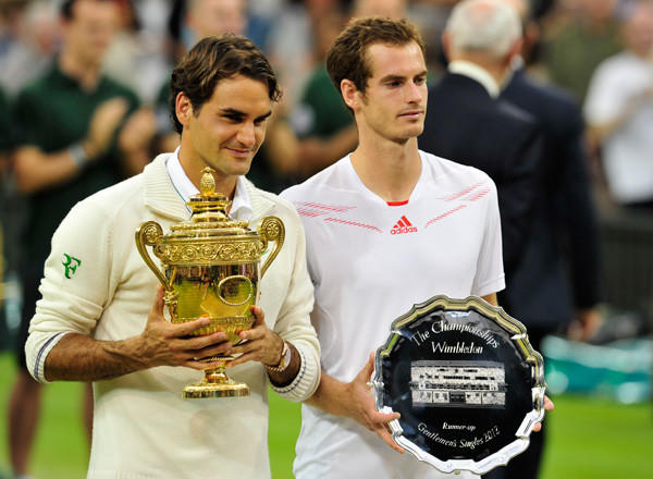 Roger Federer, left, poses with his trophy with runner-up Britain's Andy Murray, right, after his men's singles final victory on day 13 of the 2012 Wimbledon Championships tennis tournament.
