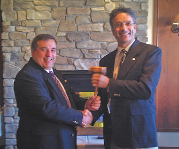 From left, Jim Mills, former club president, hands the gavel to Magnus Dahlgren, who was reinstalled recently as president of the Rotary Club of Long Meadows.