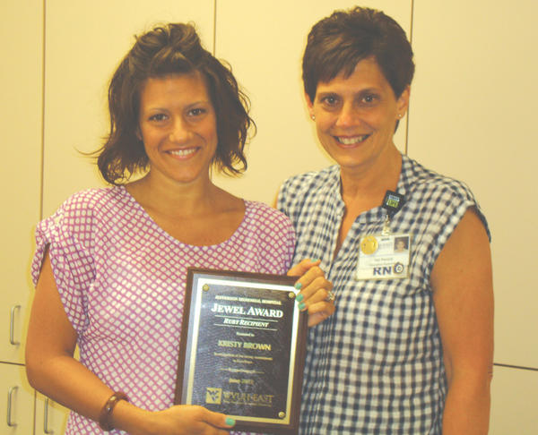 Kristy Brown, left, is presented the Ruby Award by Val Penick, education manager at Jefferson Memorial Hospital.