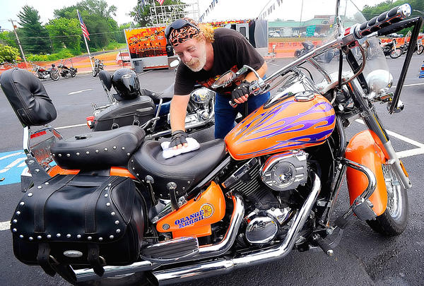 Dave Harne of Hagerstown wipes rain from his 1998 Kawasaki Vulcan named Orange Krush Sunday afternoon during the Biker Bash at Cancun Cantina West in Hagerstown.