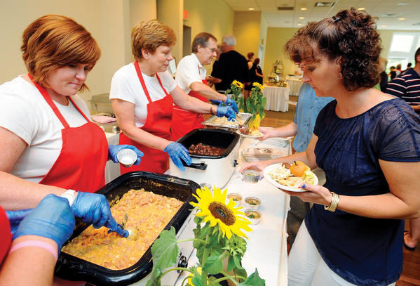Margie Rouzer, right ,enjoys food from The Kitchen Shoppe Sunday night during the Taste of The Town at the Waynesboro Country Club. Serving food, from left, are Stacy Hade, Robin Flegel, and Terry Flegel.