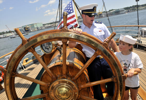 US Coast Guard Academy Cadet Matt Naylor gives Bailey Baclaski, 8, of Berlin, a lesson in steering the ship's helm aboard the US Coast Guard Eagle at OpSail 2012CT at Fort Trumbull State Park Sunday