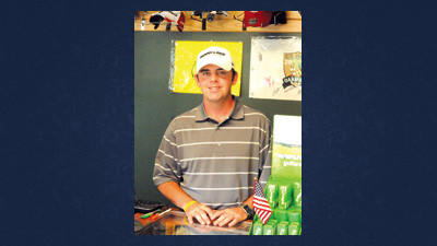 Colby Custer behind the counter in the pro shop at Indian Lake Golf Club.