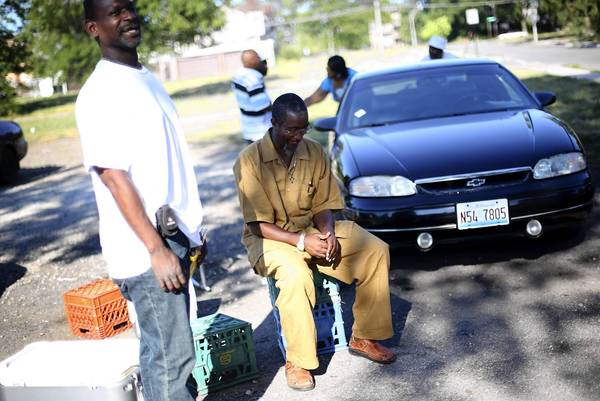 Donald Walker, of Roseland, sits with old friends from Englewood at 65th Street and Normal Boulevard in the 20th Ward. The area has had 20 homicides, the most of any ward this year. It had nine killings by this time last year.