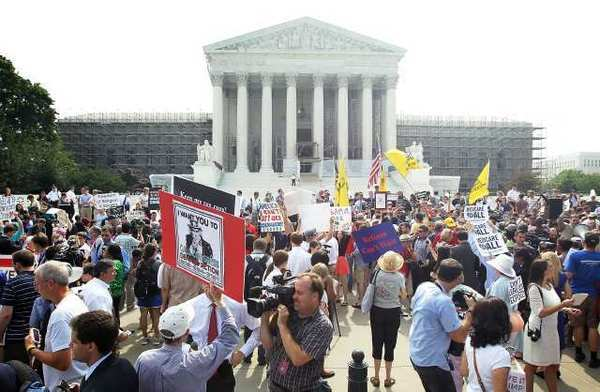 Supporters and foes of President Obama's healthcare program gather in front of the U.S. Supreme Court last month to find out the high court's ruling.