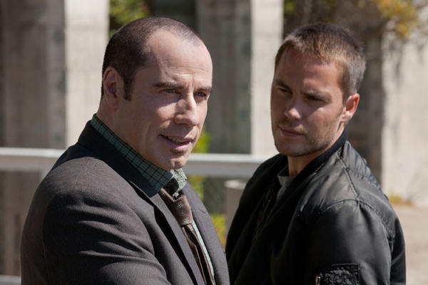 "This film image released by Universal Pictures shows John Travolta , left, and Taylor Kitsch in a scene from ""Savages."""