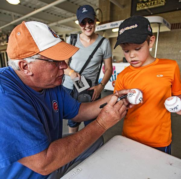 Former major league pitcher Steve Trout signs a baseball for Aidan Watson, 8, as Aidan's mom Stacey watches, at Boomers Stadium in Schaumburg. The Schaumburg Boomers play in the 14-team independent Frontier League.