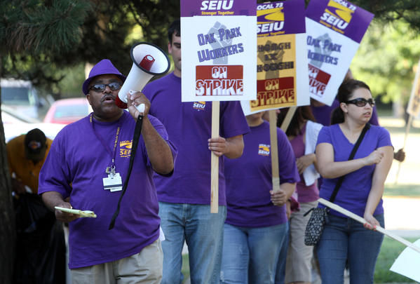 Union organizer Leonard Simpson leads the chanting with striking Oak Park village employees and SEIU officials as they picket at the Village Hall. They are seeking more than the one per cent wage increase offered by the village.