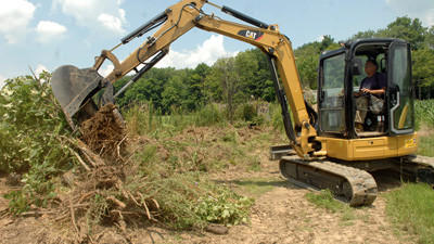 Harold Shaulis removes brush, stumps and debris along the fence row of his property in Jefferson Township on Monday.