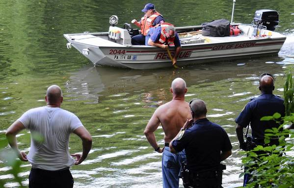 Easton police officer Anthony Chaney (left) and Lt. John Remaley, not wearing shirt, watch with other police as Easton firefighters use grappling poles to search for 22-year-old Jovanny Valdez of South Side Easton in the Lehigh River about 4:15 p.m Monday. Chaney and Remaley, the first police on the scene, jumped into the river during the search.
