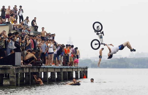 An extreme cycling enthusiast performs a stunt with a bicycle as a resident (back) jumps into the water during a diving activity at the East Lake in Wuhan, Hubei province July 9, 2012.