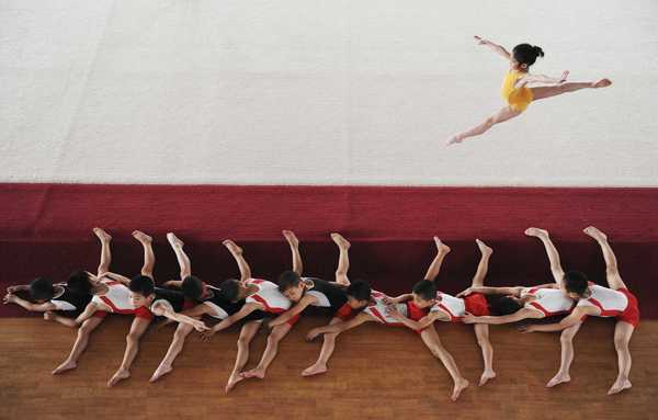 Young male gymnasts (bottom) stretch their legs as a female gymnast jumps on a stage at a local juvenile sports school in Jiaxing, Zhejiang province.