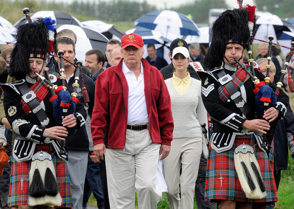 US tycoon Donald Trump (C) is escorted by Scottish pipers as he officially opens his new multi-million pound Trump International Golf Links course in Aberdeenshire, Scotland, on July 10, 2012. Work on the course began in July 2010, four years after the plans were originally submitted.