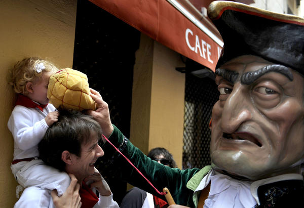 "A ""Kiliki"" hits a child with a sponge during the San Fermin festival of ""Comparsa de gigantes y cabezudos"" (Parade of the giants and the big heads) in Pamplona July 9, 2012. ""Kilikis"" wearing outsized masks, playfully hit bystanders with sponges on sticks and parade daily through the city accompanied by brass bands during the nine-day-long festival made popular by writer Ernest Hemingway."