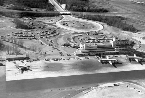 "Aerial shot of ""air side"" of Bradley terminal c. 1962, which shows many planes and has ""Bradley Field"" lettering visible but in shadow, as well as grading of new parking lot in background."