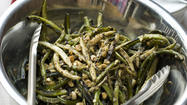Many of us grew up thinking that green beans came from a can. Those soft and water-logged beans were all we knew until we had our eyes were opened up to the true flavor of string beans (the name covers haricot verts, wax beans and green beans) that were fresh and properly cooked. But the problem is how to cook them differently. While steaming in a pan or boiling in salted water work well, it can get a little monotonous. So this time, try grilling. The dry heat evaporates the water inside the beans and concentrates the flavor while also picking up char from the flame. I use a perforated grill pan to cook my beans on the grill, but a grill basket with smaller opening works well also (in a pinch you could use your oven on broil and a cookie sheet). The key to this dish is tossing the still-sizzling string beans and scapes into the vinaigrette, which cooks the rawness out of the garlic and shallots. Garlic scapes are available at farmers' markets as well and are the curly stalks that shoot out of the tops of garlic bulbs. They are slightly garlicky and fantastic when mixed with string beans. If you cannot find scapes, substitute an equal amount of beans for them.