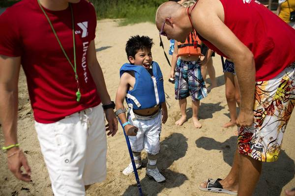 Juan Rodarte, 10, prepares for a swimming activity with staff member Mike Gardin, right, at Camp Independence. which is for campers with spina bifida, at Camp Duncan.