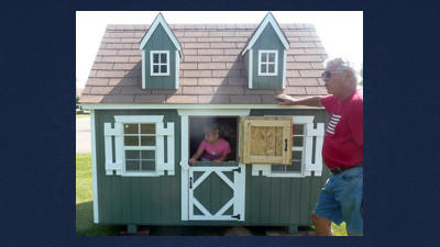 You can take home this Cape Cod playhouse. Doug Berg, Springs, looks on as granddaughter Lucy Page tries it out.