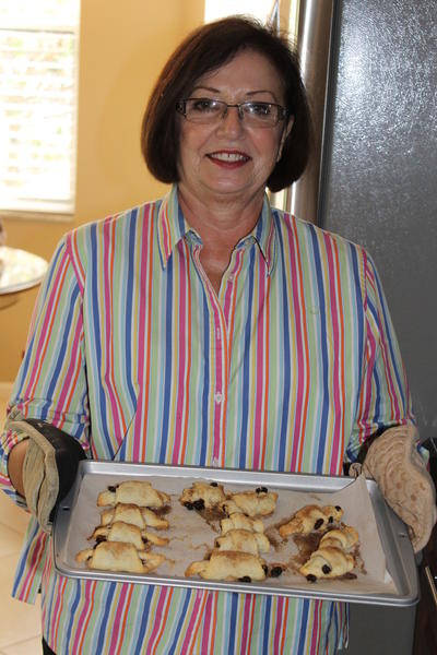 Nancy Tepper holding a freshly baked batch of her mother Mae's Cinnamon-Raisin Rugelach recipe.