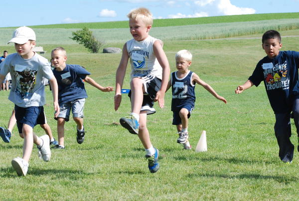First-grader Peyton Willson (center) of Petoskey leads the pack during a drill Monday at the Petoskey Little Playmakers Football Clinic at the Petoskey High School athletic fields.