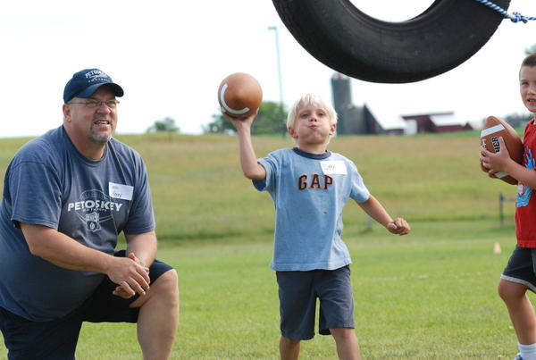 Petoskey High School varsity football coach Kerry VanOrman (left) looks on as kindergartner Drew Olson attempts to throw a ball through a tire Monday at the Petoskey Little Playmakers Football Clinic at the Petoskey High School athletic fields.