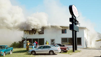 Firefighters stretch a hose in front of Featherly's Auto and Truck Service and Repair on U.S. 31 South of Charlevoix Tuesday as they prepare to fight a fire that broke out at the business around 5:30 p.m.