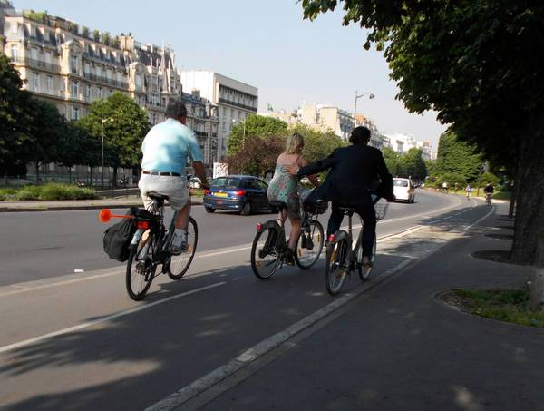 Bike riders on a street along the Seine