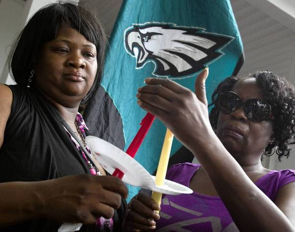 Marilyn Dix (left) and Barbara Lewis light candles during a vigil for James Wesley Dix, who was shot and killed during a robbery at the intersection of 25th Street and Parish Avenue early Monday morning.