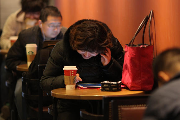 A woman looks at a computer in a coffee shop