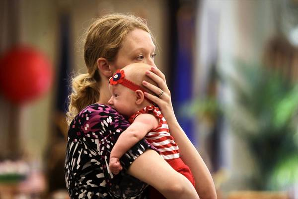 Sara Davis holds her 7-week-old daughter, Charlotte, at a baby shower Tuesday in Chicago for wives of service members. Her husband is serving in the Navy aboard the USS Enterprise.