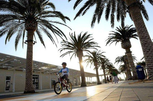 A boy rides his bike through the Palm Courts Arts Complex at Irvine's Great Park.