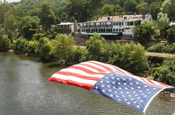 There almost always is a flag flying from the walkway of the pedestrian bridge over the Delaware River at Lumberville. The water below appears serene, but can be deadly.