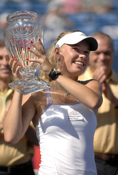 Carolina Wozniacki hoists the championship trophy after winning the Pilot Pen Tennis Tournament Saturday. Wozniacki, an unseeded player, defeated the tournament's top seed, Anna Chakvetadze, 3-6, 6-4, 6-1, to win her first WTA tour title.