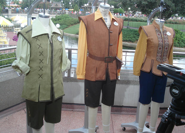Disney World previewed some costumes that cast members will wear as new areas of Fantasyland open. The left two uniforms represent Village Folks who live in Fantasyland, and they'll be seen on hosts and hostesses. The more regal costume at right will be worn by character hosts.