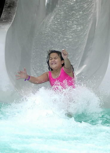 A young girl cools off on the water slide at C.B. Smith Park in Pembroke Pines. Feels-like temps could reach 100 degrees on Thursday.