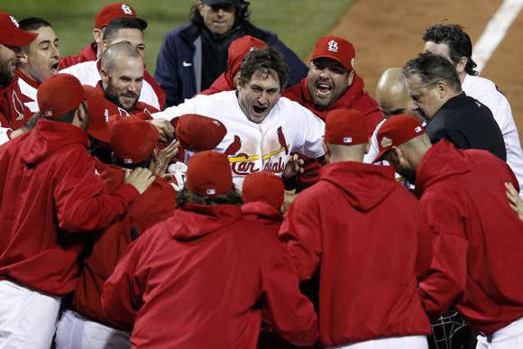 St. Louis Cardinals' David Freese, center, celebrates with teammates after hitting a walk-off home run in the 11th inning of Game 6 of the 2011 World Series.