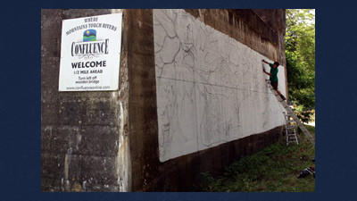 Eddie Maier of Morgantown is painting two large murals on the pillars of the Ramcat underpass along the bike trail.