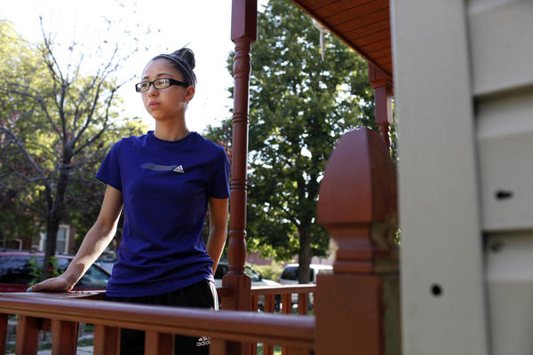 Deneysi Valdovinos, 14, stands on the porch where she and her 13-year-old friend were shot at on the 2400 block of West 47th Place in Chicago. Valdovinos and her friend were sitting on the porch when a person came up to them and started shooting. Valdovinos said her friend, who jumped in front of her, was shot multiple times. Bullet holes can be seen on the siding.