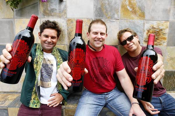 Laguna natives Steven Chew, winemaker Jeff Farthing and Brandy Faber, left to right, show off Red Siren, Purple Corduroy's debut red zinfandel, which locals have been scooping off the shelves.