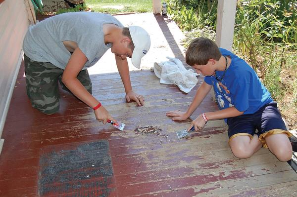 Ian Clayton, left, and Luke Ritz scrape paint off a Greencastle, Pa., porch Thursday as part of Chambersburg Project, a workcamp where volunteers help people in need.
